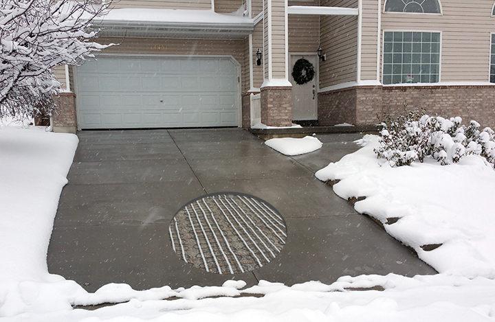 Concrete heated driveway with cutout showing heating cables.