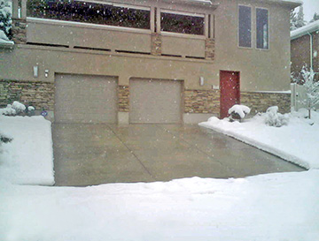 A concrete heated driveway in operation during a snowstorm.